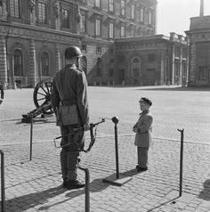 Prince Carl the future H.M. King Carl XVI Gustaf of Sweden is studying a guard at the royal castle of Stockholm Sweden. Photo: K W Gullers 1952 [1100x800]