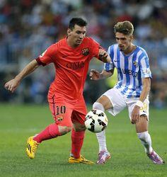 GRA596. MÁLAGA. 24/09/2014. El delantero argentino del FC Barcelona Leo Messi (i) lucha el balón con el delantero del Málaga CF Samuel Castillejo, durante el encuentro de la quinta jornada de Liga en