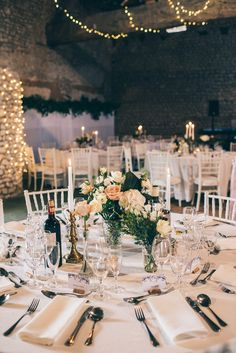Elegant Rustic Barn Reception with Flower Stem in Vase Centrepiece - Annabel Staff Wedding Photography | Marry Me in France Outdoor French Wedding at Manoir de Longeveau | Limor Rosen Wedding Dress | Coast Blush Sequin Top & Bespoke Skirt Bridesmaid Separates | Ted Baker Navy Suit