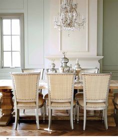 Beautifully serene and quiet dining room with French dining chairs with nailhead trim, chandelier, and stunning French fireplace. Decor de Provence.
