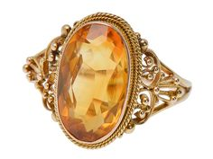 Ornate Vintage Edwardian Citrine Ring. Fantastic filigree emphasizes granulation and wire work to set off this Edwardian 10k yellow gold ring. An oval faceted citrine of 2.3 carats coordinates its golden amber color with the warm glow of the ornate mounting.