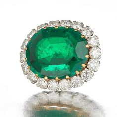 An emerald and diamond brooch/pendant   The central cushion-shaped emerald, weighing 18.85 carats, within a border of brilliant-cut diamonds