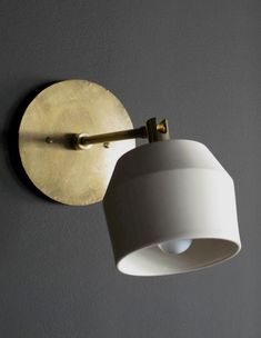 Designed by Materia Designs Available Porcelain: Graphite or Natural Porcelain with Brass Metal Finishes: Unlacquered Brass Custom Charge Metal Finishes: Aged Brass, Aged Silver, Blackened Brass Sconce: - L x W Shade: Diam x H Canopy: Dia Shop Lighting, Lighting Design, Pendant Lighting, Lighting Ideas, Brass Sconce, Concrete Lamp, Plywood Furniture, Wall Sconces, Wall Lamps