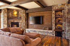 I was thinking of some kind of built-in to hide the tv with a sliding panel, but this wood wall surrounded by stone is kind of striking. The adjacent shelves with stone and wood could give you some display space.
