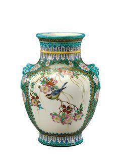 THEODORE DECK (1823-1891) Vase à corps ovoïde et col évasé reposant sur un talon légèrement évasé en céramique émaillée polychrome à décor foissonnant de fleurs, d'oiseaux, de lambrequins et de papillons présentant en relief deux mascarons imitant des anses. Signé du cachet «TH.Deck». Vers 1880-1890.