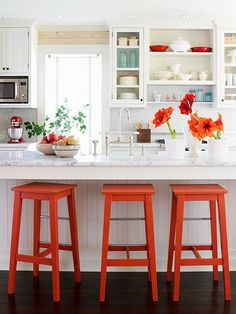 Bold orange accents liven up this all-white kitchen.
