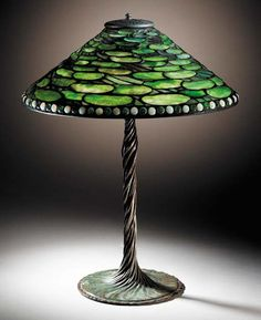 A 'LILY PAD' LEADED GLASS AND BRONZE TABLE LAMP   Tiffany Studios, circa 1910   25½in. (64.3cm.) high, 20in. (50.3cm.) diameter of the shade, with finial  the shade tag stamped TIFFANY STUDIOS NEW YORK 1502-20, the twisted vine base stamped TIFFANY STUDIOS NEW YORK 443