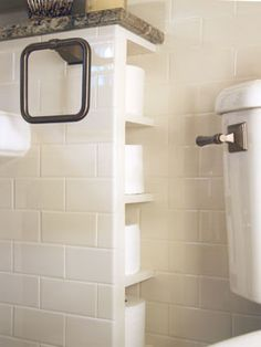 For a creative (and hidden) storage solution, tiny shelves built into a partition near the toilet hold multiple rolls of toilet paper in a convenient location.