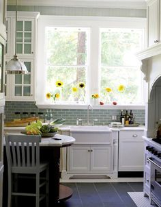 so much goodness in such a small space #kitchen #home #aqua #tiles #oven #appliance #sunflower #flower #yellow #white #cabinets