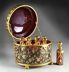 "treasures-and-beauty: "" Glass perfume casket by Moser, of circular form holding twelve individual perfume bottles, the whole decorated with gilt floral and fauna decoration and raised on ball feet, each bottle with highly polished pontil, circa late..."