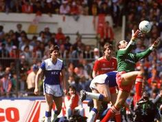 Liverpool v Everton at Wembley in the 1986 FA Cup final.  Liverpool goalkeeper Bruce Grobbelaar (right) comes out to claim the ball, watched by Everton's Gary Lineker (left) and Liverpool's Ronnie Whelan (centre)