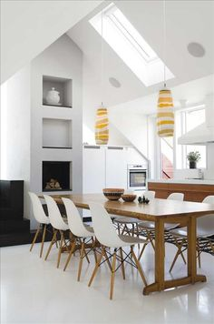 Eames chairs at the kitchen table, with a great style in the lights and simple decor.