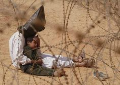 Award winning photo showing a iraqi man comforts his son at a holding center for prisoners of war in An Najaf, Iraq, 31 March 2003. AP photographer Jean-Marc Bouju has won the 2003 World Press Photo of the Year competition. Jean-Marc won also the 1995 Pulitzer Prize in Feature Photography and the 1999 Pulitzer Prize in Spot News Photography.
