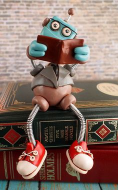 Professor Bot Bixbo Robot Sculpture: this smartly dressed robot sitting neatly engrossed in a good book, dressed in a necktie and gray coat wearing black eyeglasses along with red sneakers for a touch of hipster. Bixbo is an awesome companion for your desk, bookshelf or gift for a nerdy smarty pants in your life, $60.00