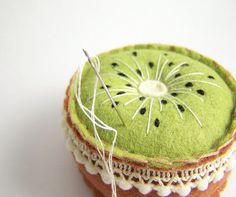 Felt Kiwi Pincushion Embroidered by Sea Pinks on Etsy | This is a cute round pincushion made of pretty light green and soft copper brown wool blend felt, trims with cute little pom poms. A perfect gift for the kiwi lover in your life, or just someone who really likes fruit!