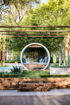 This award winning garden design uses concrete pipes to create seating, a water feature, and a fire pit. More