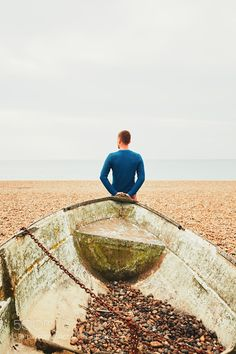 Alone and pensive man on the beach leaning against old broken ship.