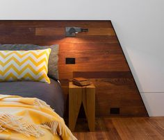 Bed and wooden wall behind Stonewood Suburb House in Melbourne by Breathe Architecture