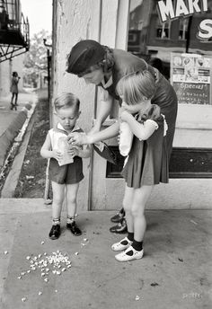 "October 1938. ""Mother and children with popcorn, National Rice Festival, Crowley, Louisiana."" Valuable practice for the Popcorn Festival. 35mm nitrate negative by Russell Lee for the Farm Security Administration. View full size."