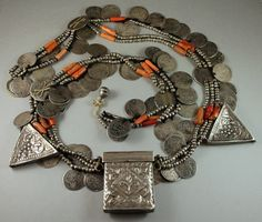 """Antique Algerian Kabyle Necklace  This is a spectacular, complete and rare necklace called """"tazlagt umm lherz"""" meaning strung elements with a prayer holder.  This necklace has three twisting strands of tiny faceted beads and coral which string through large coins and three hirz amulets. Around these three strands is a fourth strand of smaller coins which twists from strand to strand.  Coins date from the 1700s through 1906."""