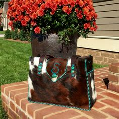 A Buckaroo Diaper Tote stitched in turquoise leather lace, with side pockets lined in suede, turquoise stones and a turquoise suede S on the flap. From gowestdesigns.us