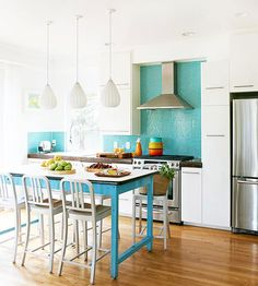 A slim industrial-style island is a perfect fit in this contemporary kitchen. Bold blue paint on the island and a bright backsplash combine forces to create a fresh place to cook! http://www.bhg.com/kitchen/island/colorful-kitchen-islands/?socsrc=bhgpin010415seasidebluekitchen&page=7