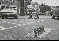 Students taking a crosswalk in the 1970s. Note the sign coming up from the pavement! SMTTT!