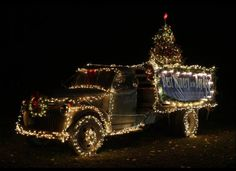 An old truck and Christmas tree are decorated with lights outside the V. Sattui Winery in St. Helena, Calif.