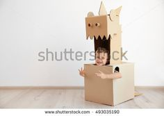 Little boy playing with cardboard box on white wall background