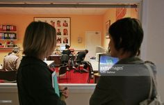 Two women view an artwork installation of a working production office called 'shady lane productions' by artist Phil Collins, which will research a British episode of 'the return of the real' over the course of the exhibition during a preview of The Turner Prize 2006 at the Tate Britain on October 2, 2006 in London, England. The Turner Prize honours the achievements of an outstanding artist, living and working in Britain. The winner of the prize will be announced on December 4, 2006.