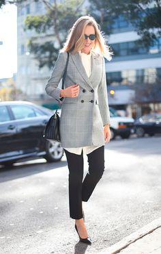 Mulher loira sorrindo atravessa a rua usando camisa off white com laço no pescoço, blazer oversized de botões xadrez, calça cigarrette preta, scarpin preto e bolsa a tira colo
