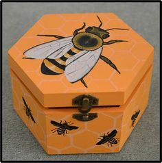 Honey Bee Wooden Box This hand painted wooden box features a honey bees on a honeycomb pattern design. Great for storing trinkets, craft bits and jewellery, amongst other things! Or perhaps perfect as a gift box for someone who loves honey or beekeeping! Great for everyone who likes