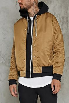 A woven bomber jacket featuring a contrast ribbed trim along the basic collar, long sleeves, and hem, a snap-button placket, front slant pockets, and an interior slip pocket.