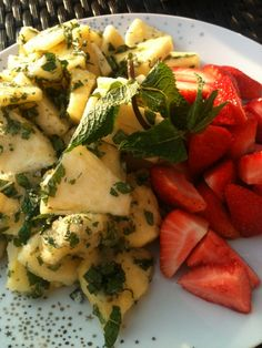 Fruit desert; strawberry and pineapple with sugar and mint leaves