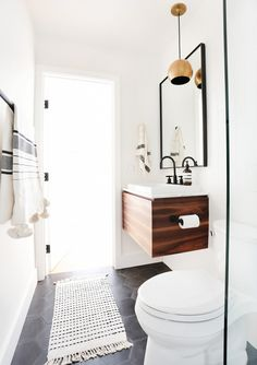 Minimalist-inspired bathroom with a floating wood vanity with a white vessel sink, and a gold pendant light