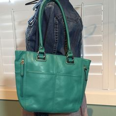 Tignanello teal leather tote purse Like new condition, used only a couple weeks. Clean inside and out! Super cute and Ready for Spring! 11 in height, 11.5 wide, 5 in sides, strap drop 10.5 in. Outside one later zippered compartment on back, two zippered compartment on front sides, two large pockets on front . Inside three compartments, one is zipper d in center, cell phone pockets and one zippered compartment on back wall. This purse is perfect for organizing and fits a lot of STUFF ❤️…
