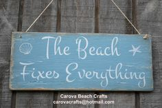 """This hand painted (no vinyl) wood sign reads- """"The Beach Fixes Everything"""" It measures 14"""" x 6"""" and painted coastal blue, antiqued and distressed for that rustic finish. Jute rope is attached for easy"""