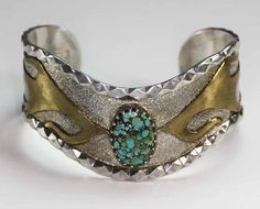 Vintage sterling silver cuff bracelet has a spider web turquoise cabochon and brass abstract flame-like design on the sides Cuff has a