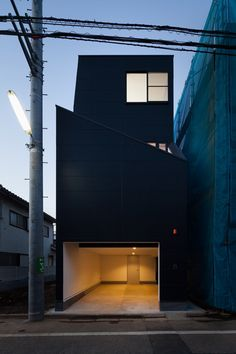 apanese studio Level Architects squeezed this all-black house onto a narrow plot in Tokyo's Fukasawa district, adding sloping offset walls around the lower floors to protect residents' privacy