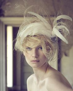 A white scull capped headpiece with feathers and a Swarovski crystal detailing.   Photo courtesy of Jane Taylor Millinery.
