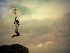 Umbrella jump over a cliff.
