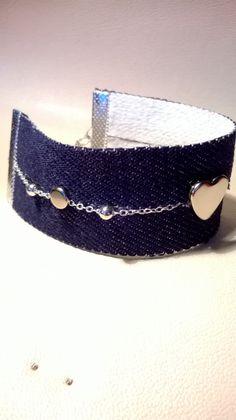 CREA 45 : Bracelet manchette aspect jeans avec une chaînette au milieu et 3 attaches incrustées dont une en forme de coeur.