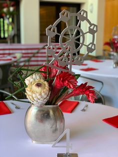 Custom centerpiece picks elevate this modern design with ginger and white protea.