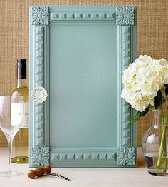 Add interest to a plain cabinet door by parading pretty trimwork around the door's perimeter. Measure your cabinet door to determine how much molding you'll need. Be sure to factor in the size of the four embellishments for the corners. Use a miter box to cut the molding strips to size. Paint the cabinet, molding, and embellishments the same color. When they are dry, use wood glue to affix the molding and embellishments to the cabinet. Clamp the pieces in place until the glue dries.