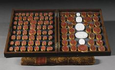 A collection of George III wax and glass seals late 18th century, by James Tassie comprising ninety one was seals and five coloured glass seals, all depicting classical subjects, some labelled and contained within a mahogany  case in the form of a book fastened by a sliding gilt-tooled leather covered spine entitled `SELECT GEMS' , together with a collection of sixty seven coloured glass intaglios and seals also by James Tassie