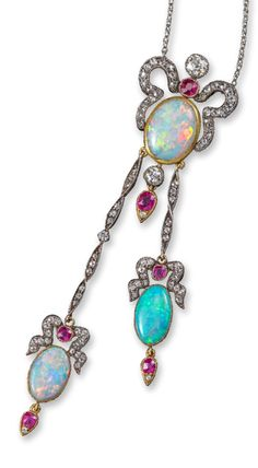 An Edwardian opal, ruby and diamond lavalier, the solid white opal cabochon within diamond scroll surround and ruby and diamond drops suspends two articulated matching pendants, in silver and yellow gold, on fine-link platinum neck chain with an opal set to the clasp, pendant 10.5cm long, chain 45cm long.