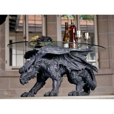 """Award-winning artist Moore, well-known for his fantasy art and sculpture, has tamed this wild 35""""-long beast to serve your guests in a creative union of style and function! His most unique approach to decorative dragon art yet, our 52 lb. Toscano exclusive is sculpted 360-degrees and topped with a 3/8""""-thick, pencil-edged oval glass top so he can be admired from all angles. This finely hand-painted, quality designer resin dragon is ready to serve and protect! 39""""Wx22""""Dx18""""H. 52 lbs."""
