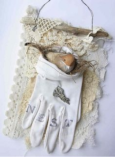 """beautiful - bird nest in the """"pocket"""" of a vintage glove backed with lace, mounted on driftwood, hung from wire loop"""