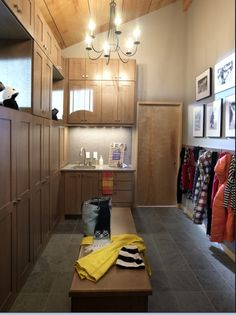 Mud room ideas. I like the bench in the middle instead of on the wall where all the hooks and cupboards are.