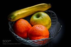 Fresh fruits by VirginiaPuschkarow from http://500px.com/photo/198515977 - Apple oranges and a banana in a glass bowl for healthy nutrition. More on dokonow.com.